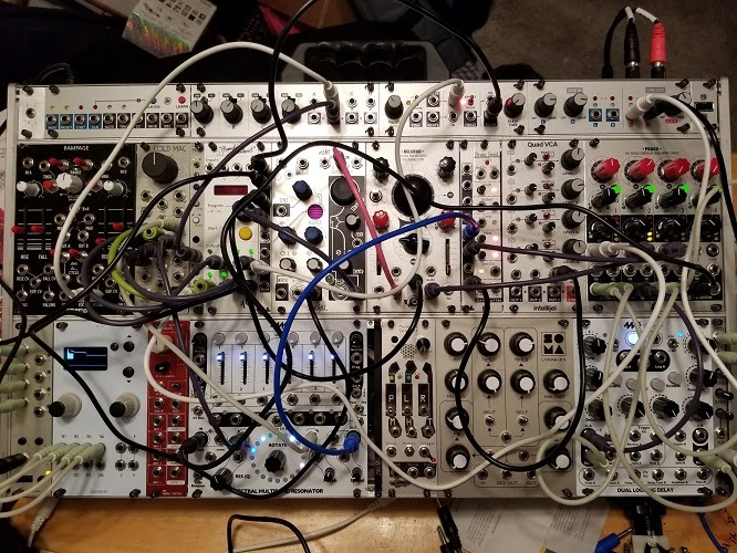 A board used for making electronic music, covered in cables, knobs, and sliders
